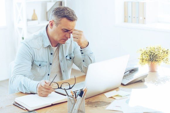 Mature man sitting at computer looking frustrated