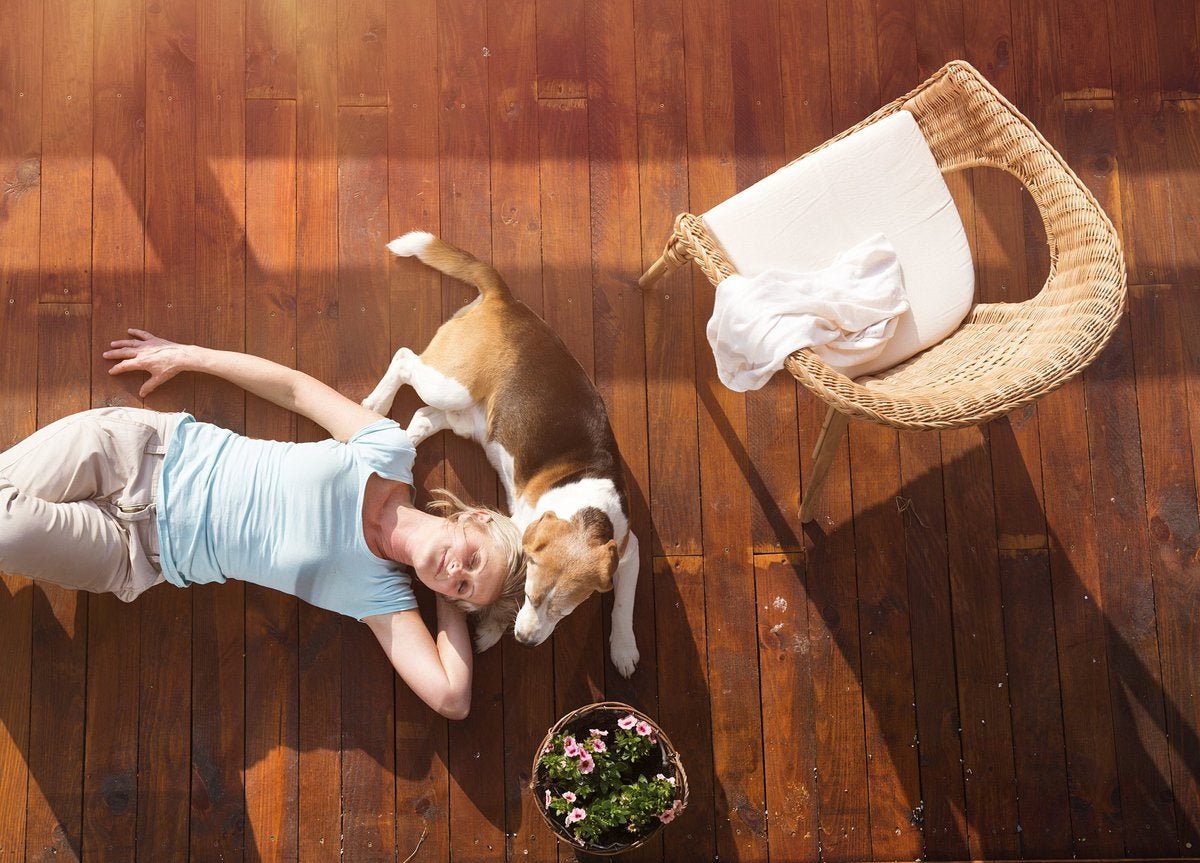 Mature woman lies down on a deck with her head resting against her beagle