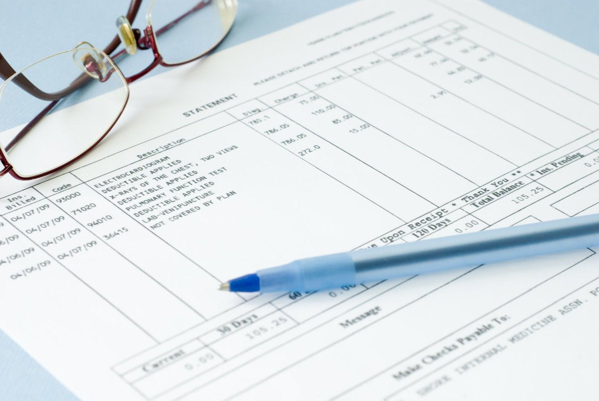Medical bill with glasses and pen