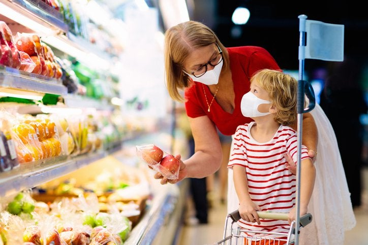 A mom and her young child shopping for fruit while wearing masks in a grocery store.