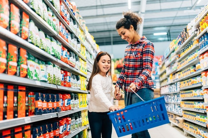 A mom and daughter walking down the aisle of a grocery and putting food in their basket.