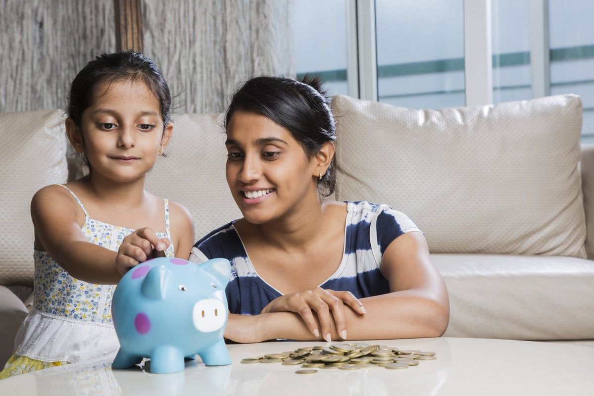 A young girl putting coins in her piggy bank as her mom looks on proudly.