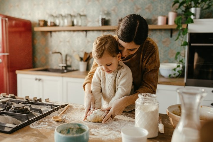 A mom and her toddler son rolling out dough on a kitchen counter.