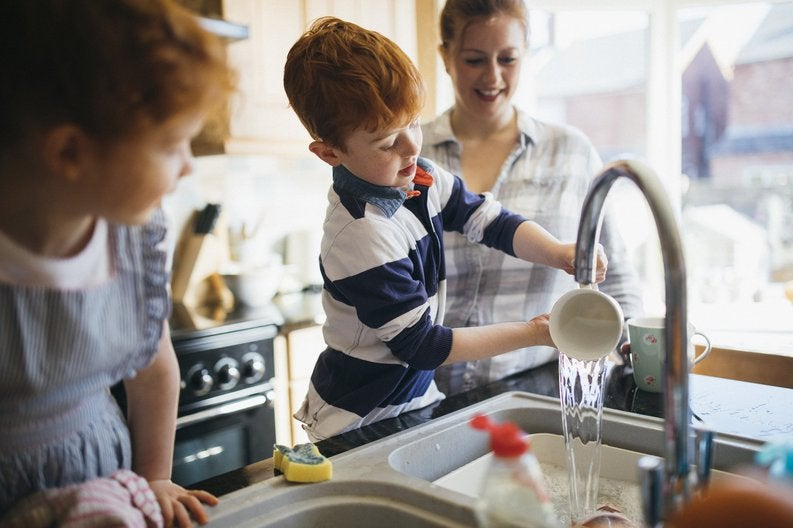 A mom and her two young children washing dishes in a bright kitchen.