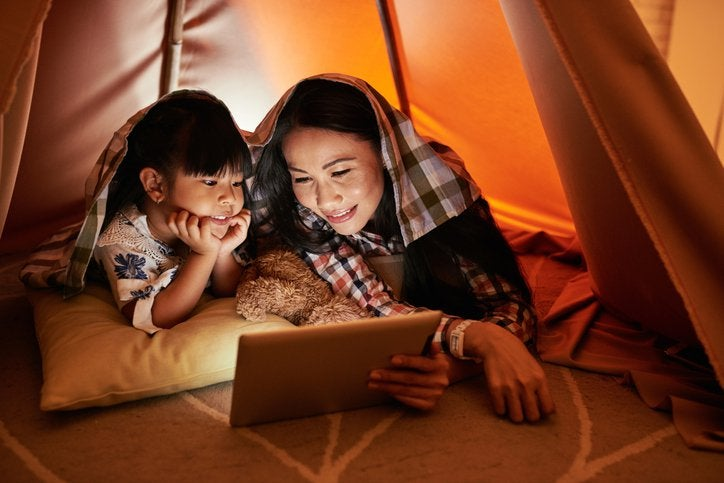 A mom and her young daughter laying on the floor in a blanket fort and watching a movie on a tablet.