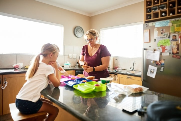 A mom standing at a kitchen island packing lunch boxes for her daughters who are sitting on stools watching.