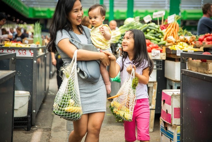 A mom carrying her baby while her daughter walks next to her through the produce section of a grocery store.