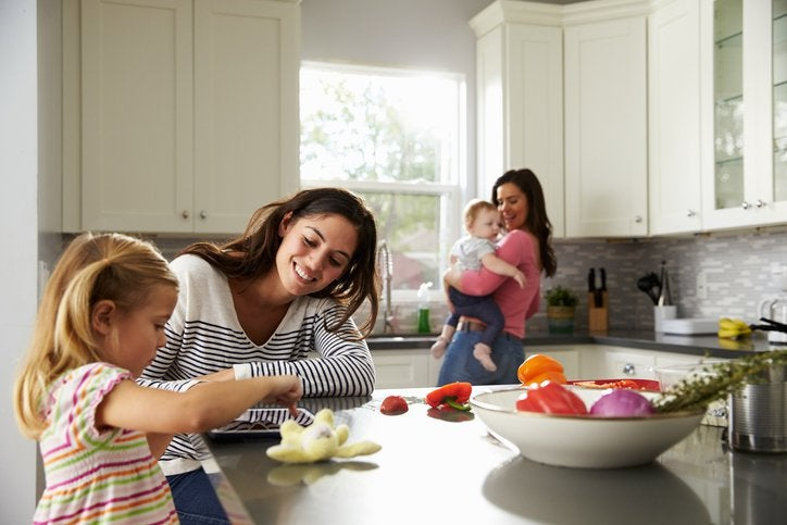 A mom playing with her daughter at a kitchen counter while the other mom dances with their baby in the background.