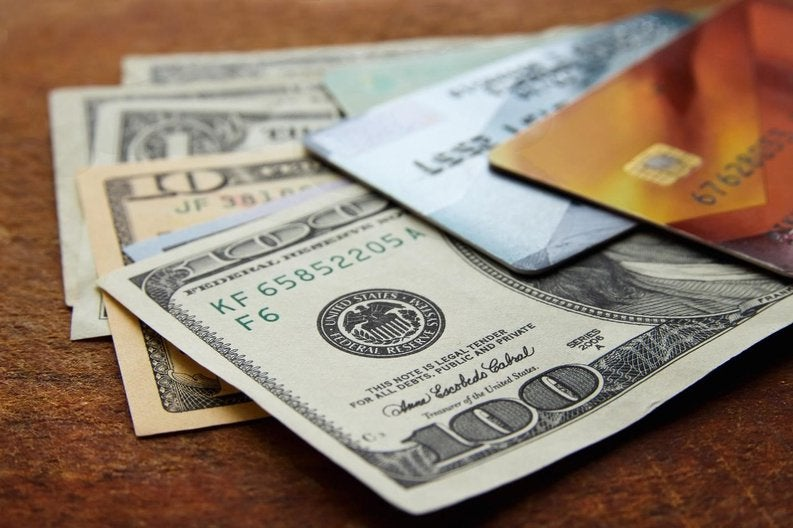 Two credit cards sitting on top of various American dollars.