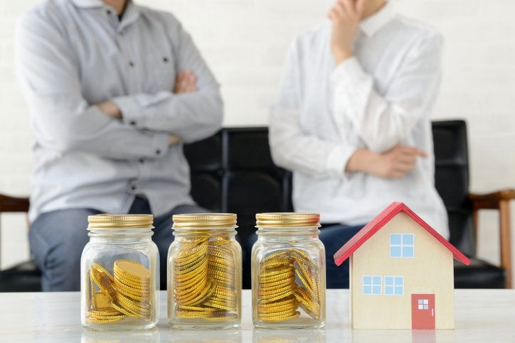 Two men blurred in background look at jars of coins and a small house