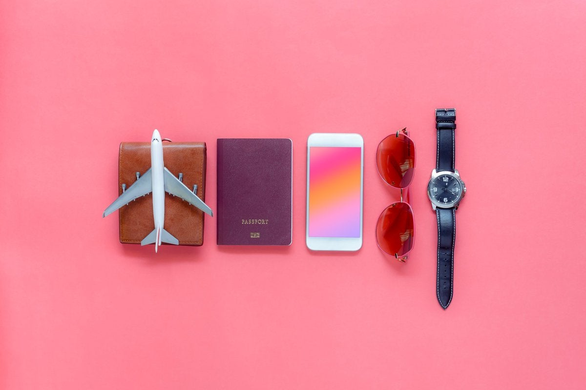 A wallet, toy airplane, passport, phone, sunglasses, and watch on a pink background.