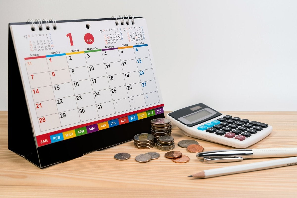 A spiral bound desk calendar turned to January sitting beside coins, a calculator, and writing utensils.