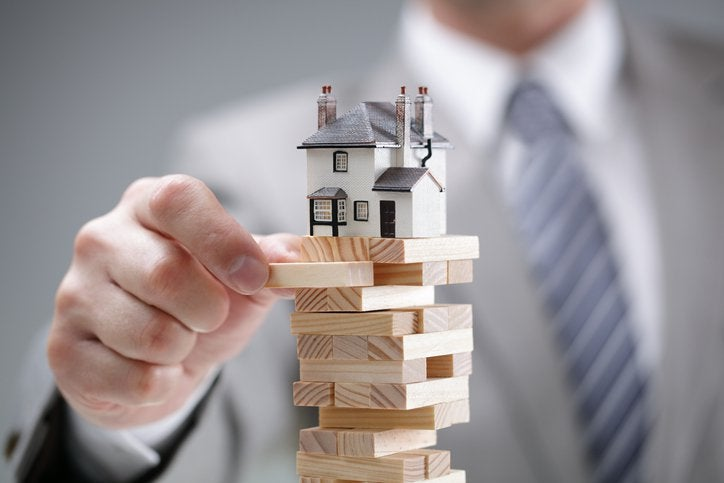 A man removes a Jenga block from a stack of blocks with a house on top.