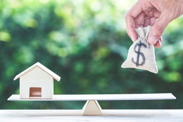 A hand places a bag with a dollar sign onto scales with a toy house on the other side.