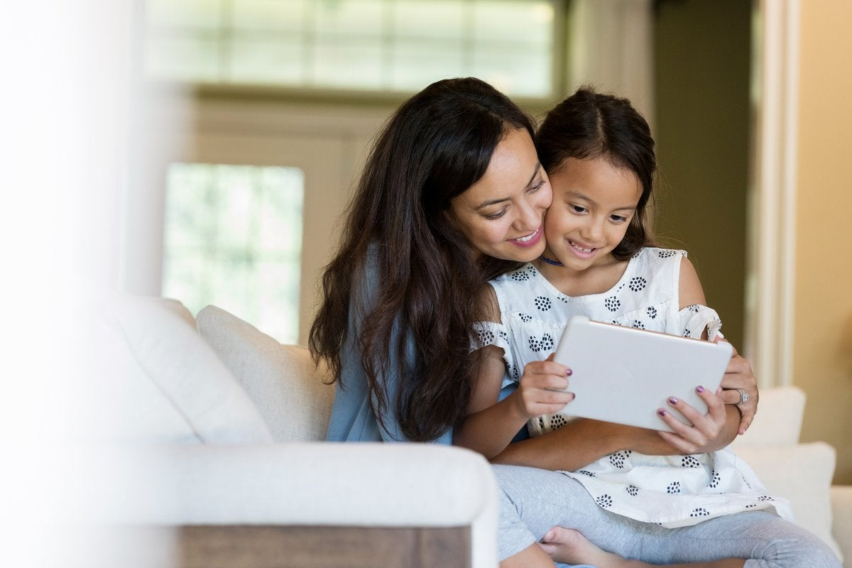 A mother and her young daughter cuddling on the couch while looking at a tablet computer.