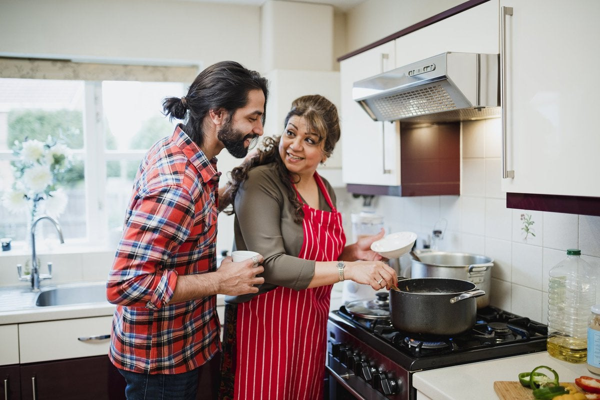 A mother cooking at the stove with her adult son looking over her shoulder.