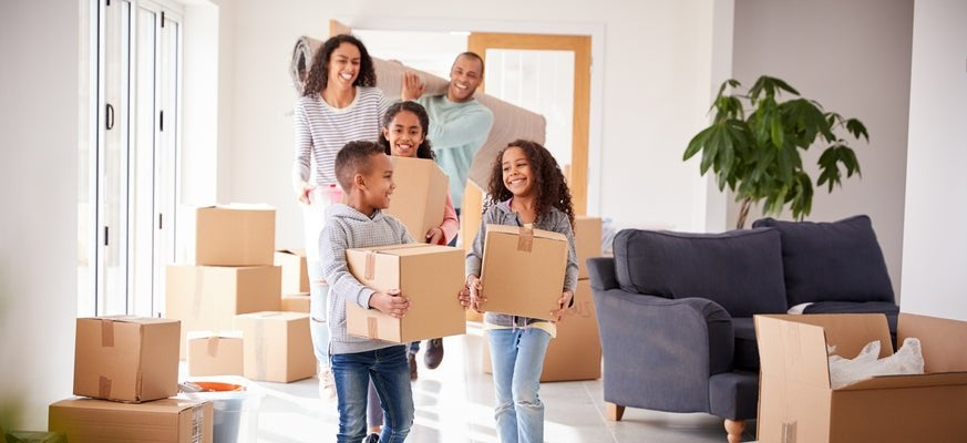 A family bringing moving boxes into a house