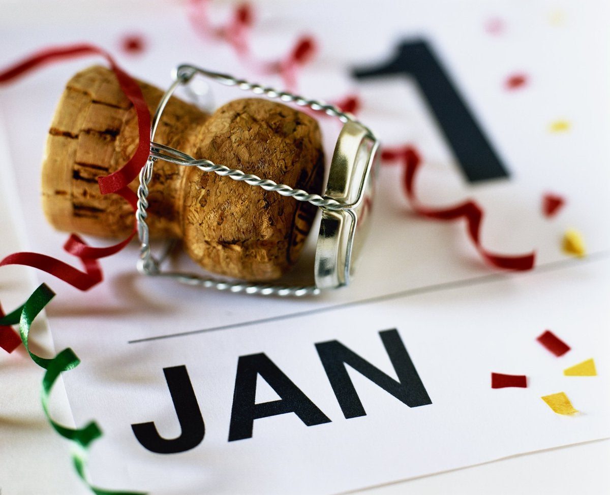A cork sitting on a calendar that says Jan. 1 with confetti on it.