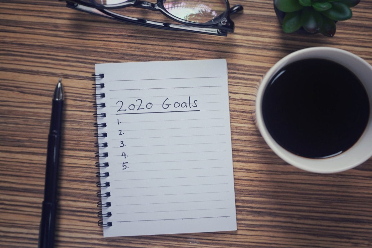 A wooden desk with a pen, cup of coffee, and a notebook that has the words 2020 Goals and a numbered list written on a page.