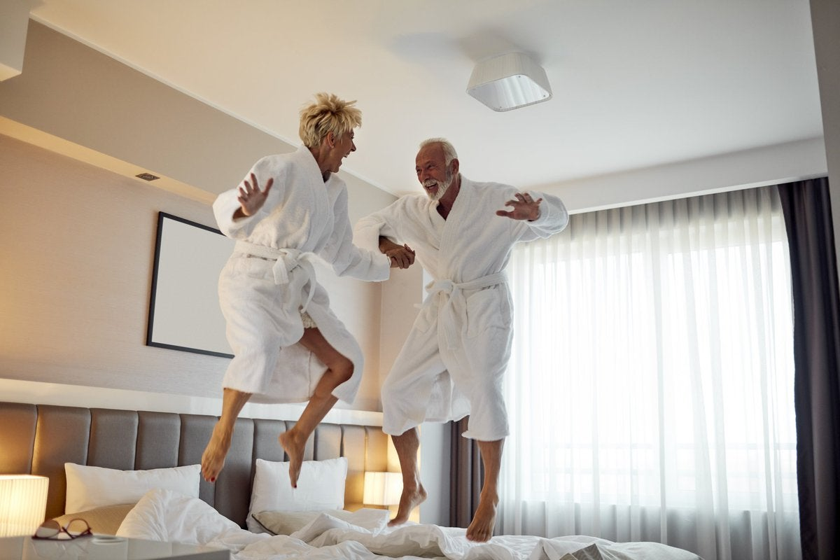 An older couple jumping on the bed in hotel bathrobes.