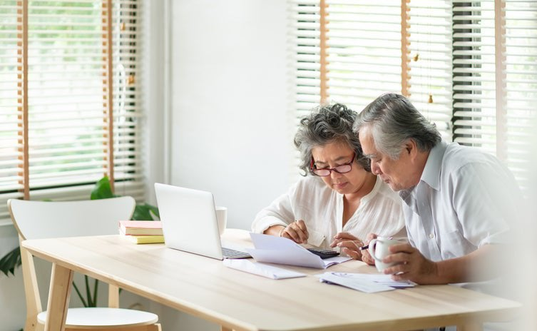 An older man and woman sitting at their dining table and looking through paper bills with a laptop open in front of them.