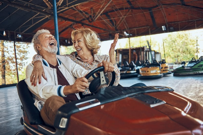 An older couple laughing while riding bumper cars at a carnival.