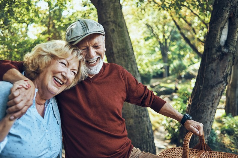 An older couple smiling with their arms around each other and holding a picnic basket in the woods.