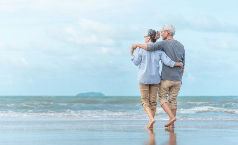 An older couple walking along the beach with their arms around each other.
