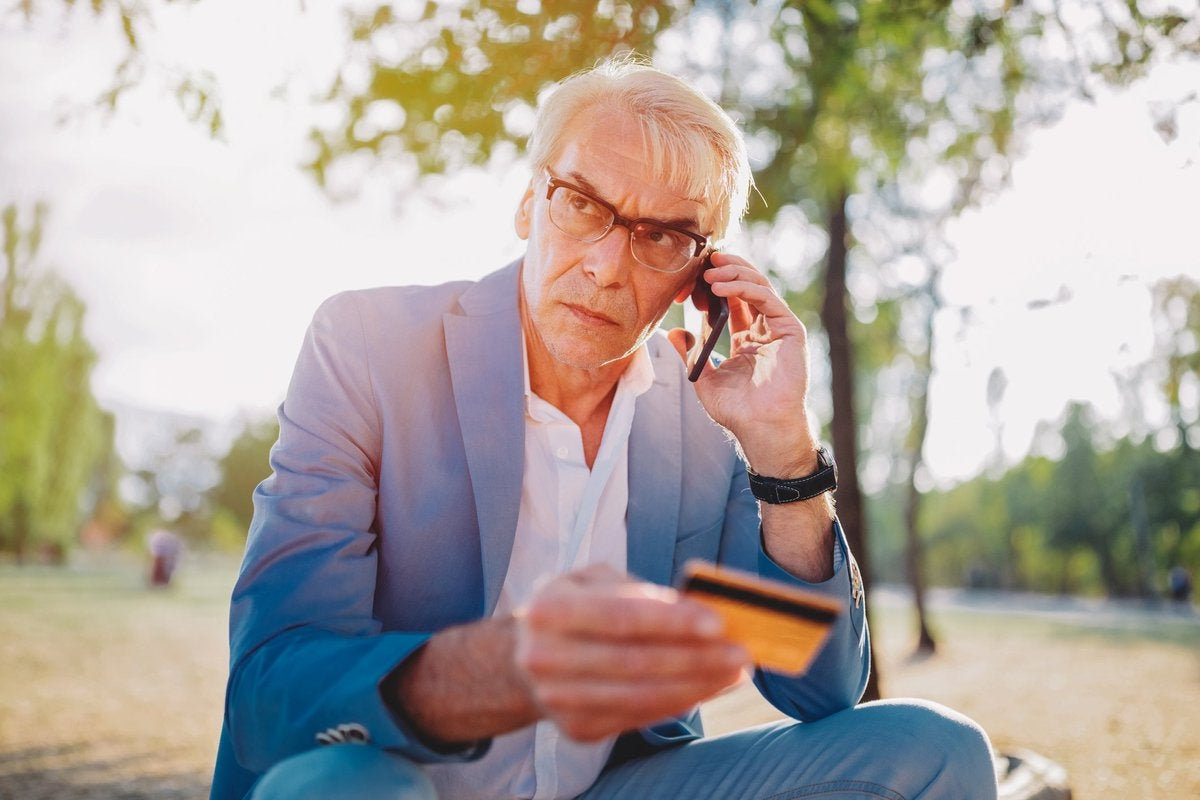 A distraught man sitting in a park and talking on his phone while holding a credit card.