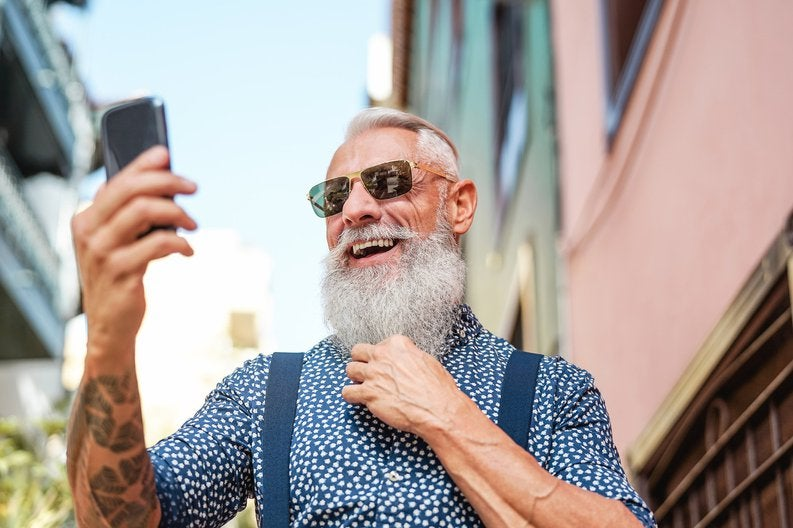An older man with a long gray beard and tattoos taking a selfie.