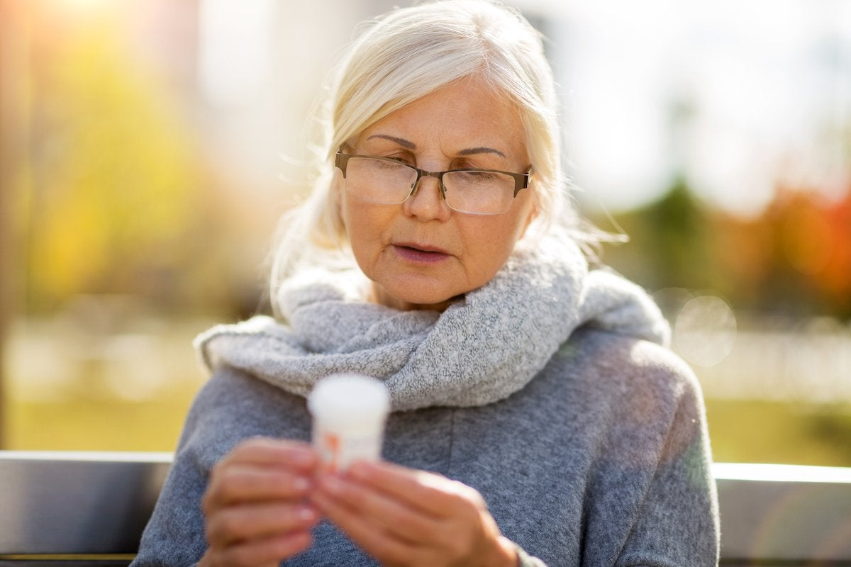 An older woman sitting on a sunny park bench and reading the label on a prescription pill bottle.