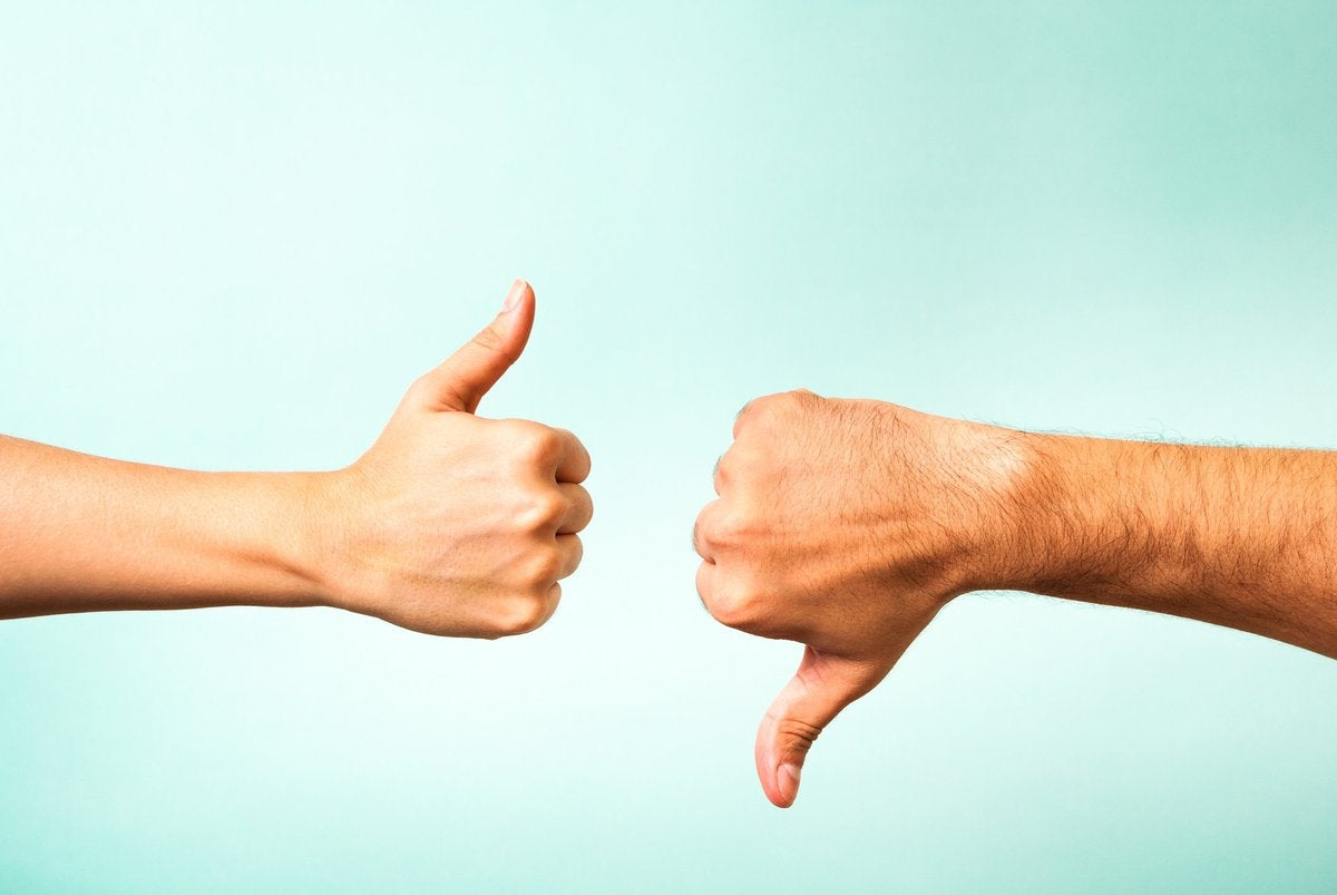 one hand giving a thumbs-up and another giving a thumbs-down
