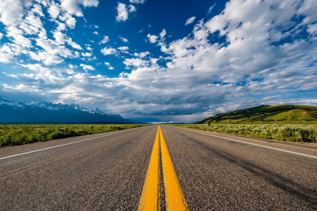 open road in Wyoming with green hills on one side and snow-capped mountains on the other