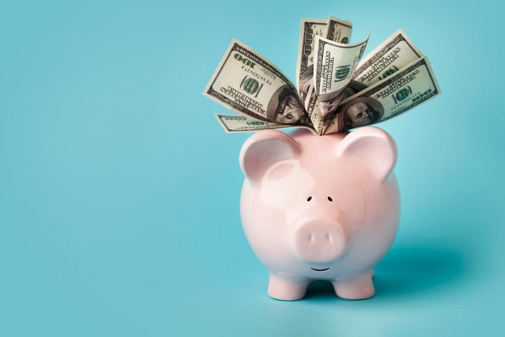 A piggy bank with hundred-dollar bills sticking out the top.