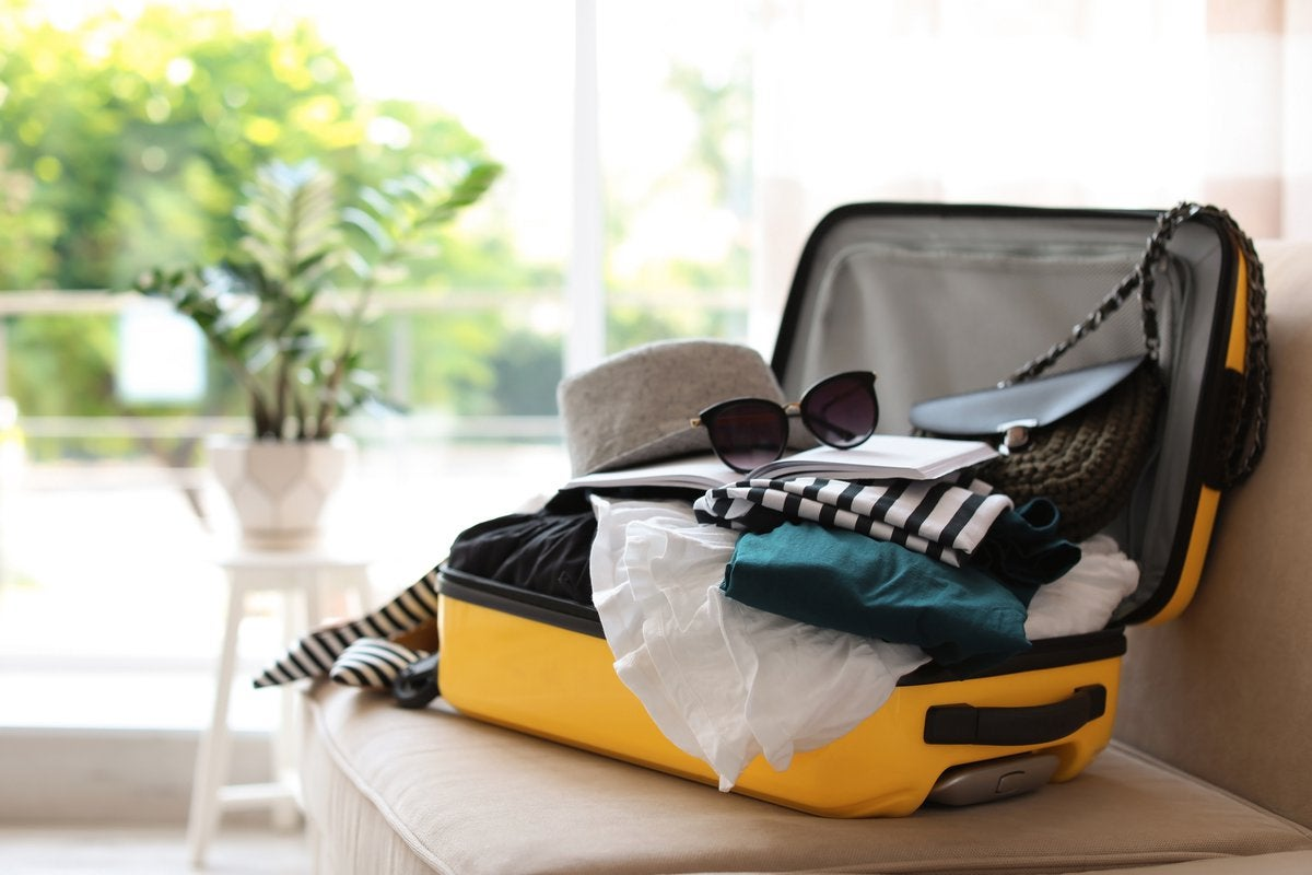 A suitcase packed with clothes sitting open in front of a sunny window.