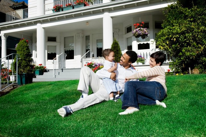 A mom and dad with their baby sitting on the sunny lawn in front of their house.