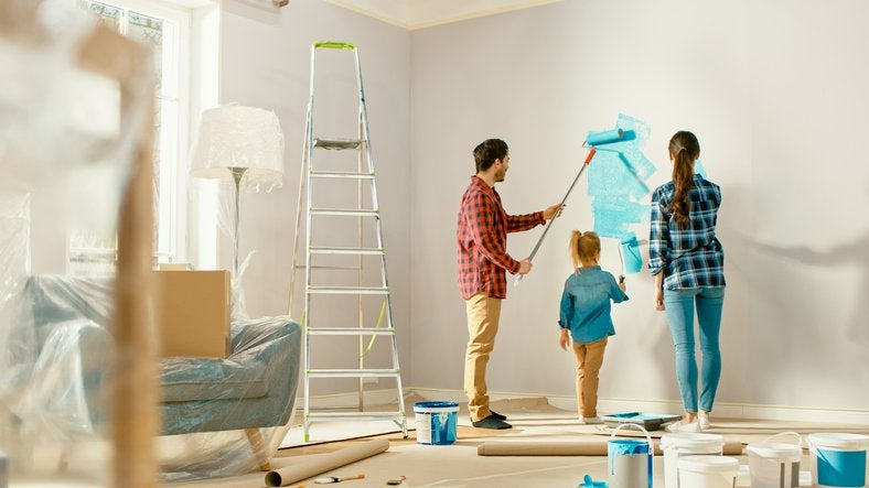 A mom, dad, and their young daughter painting the wall of their living room blue.