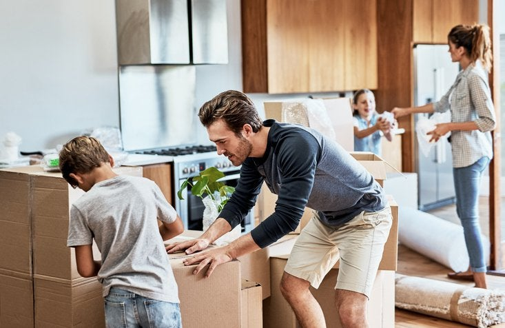 A mom, dad, son, and daughter packing moving boxes in the kitchen.