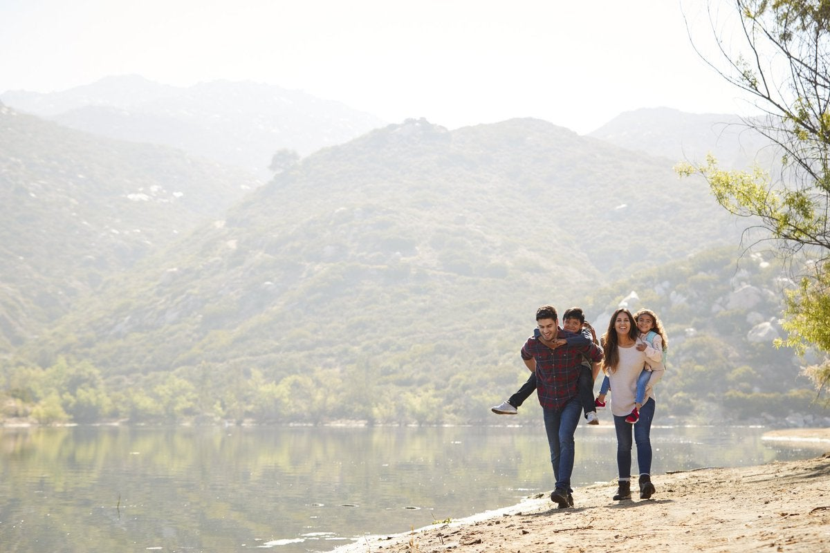 Two young kids piggybacking on their parents as they hike next to a lake with hills in the background.
