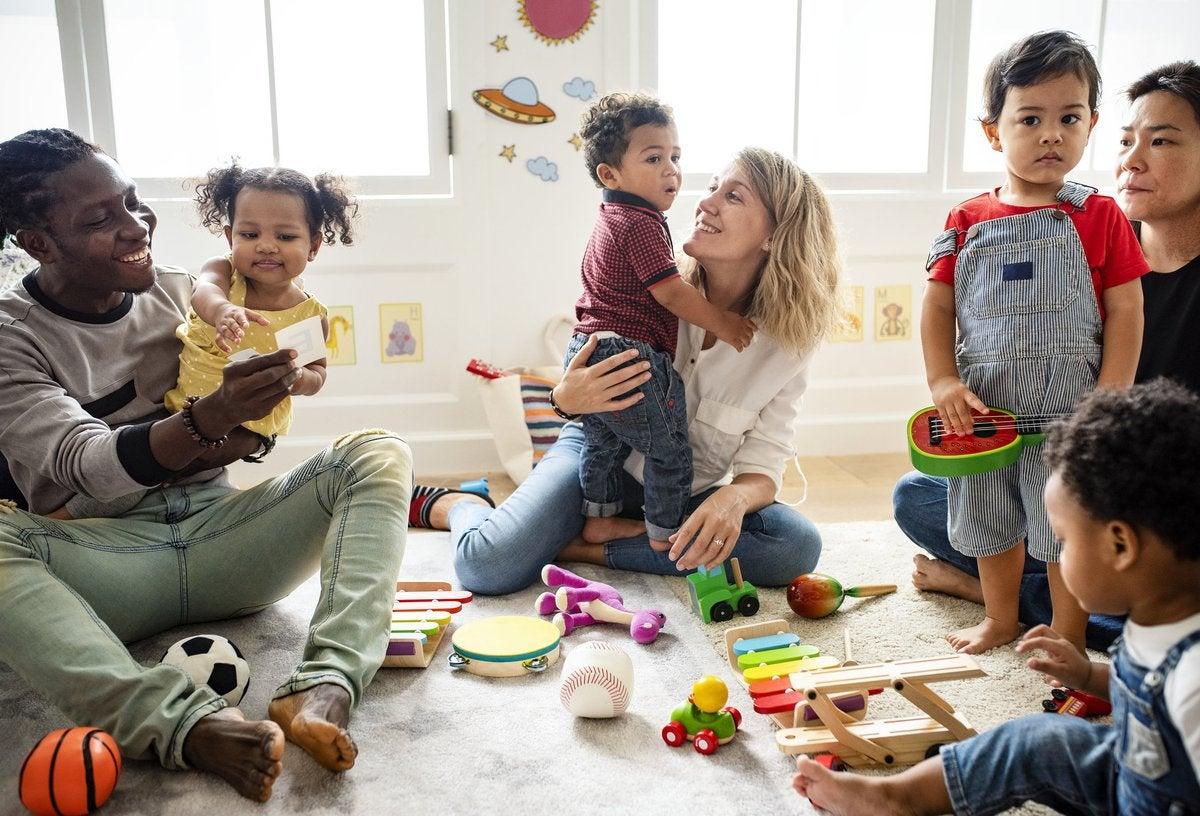 Smiling parents playing with their young children in a preschool classroom.