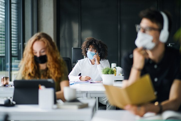 Three people wearing medical masks while seated apart and working in an office.
