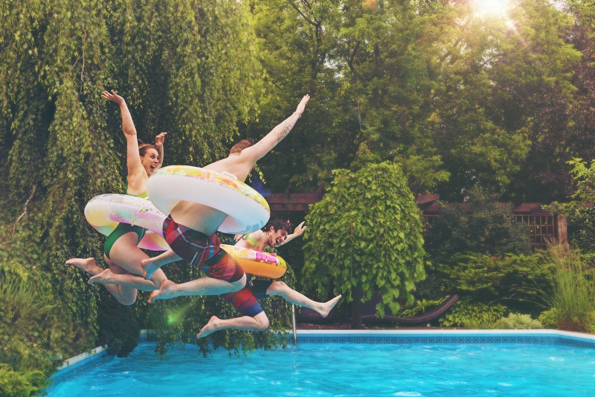 Three people wearing colorful tubes around their waists jumping into a backyard pool surrounded by trees.