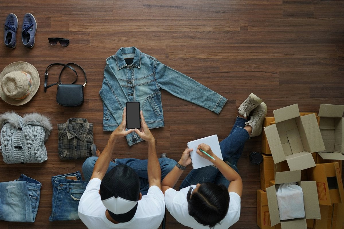Two people sitting on the floor and taking pictures of their used clothes to sell.