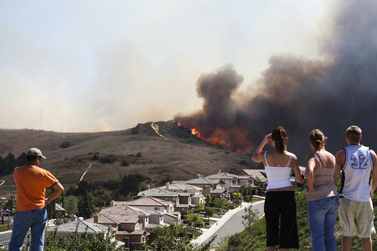 Four people watching a brush fire burn on a hill behind a street lined with houses.