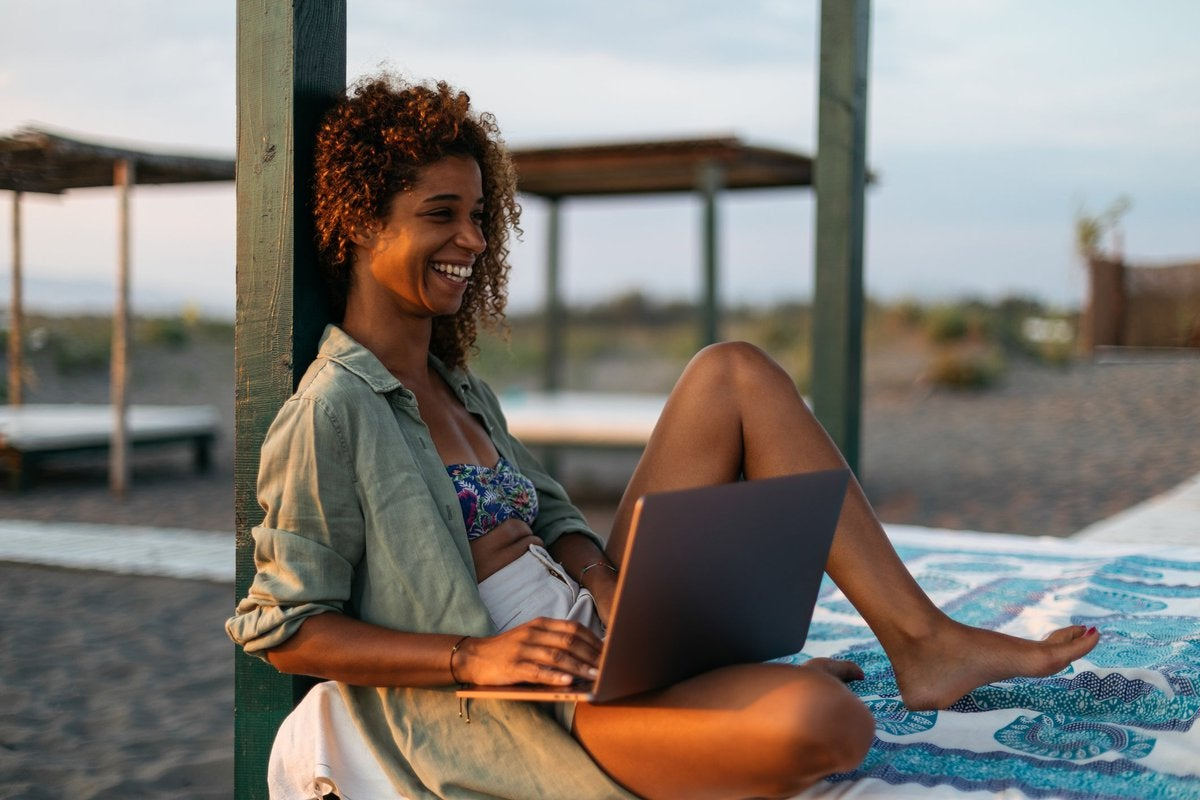 A smiling person sitting on a cabana bed on the beach while typing on a laptop.
