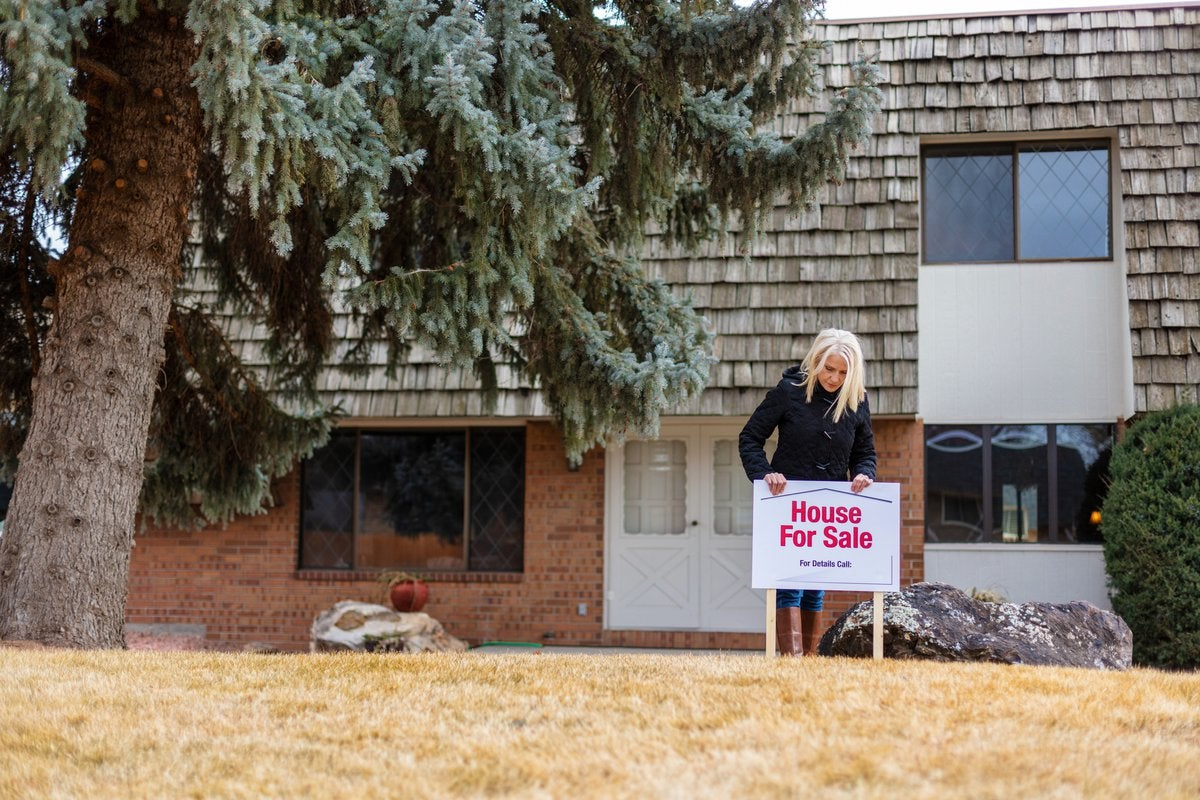 A person putting a House for Sale sign in the front lawn of their property.