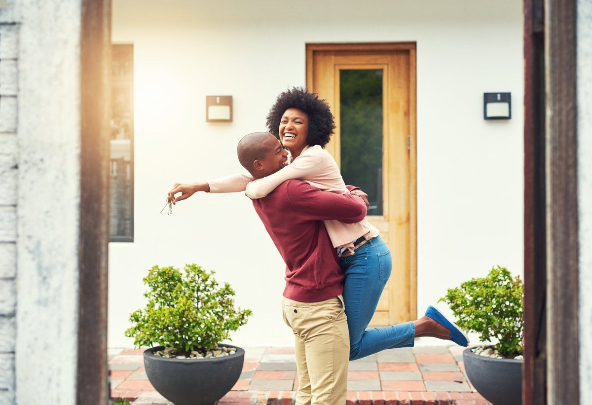 A person lifting another person in their arms who is holding keys to the new house behind them.