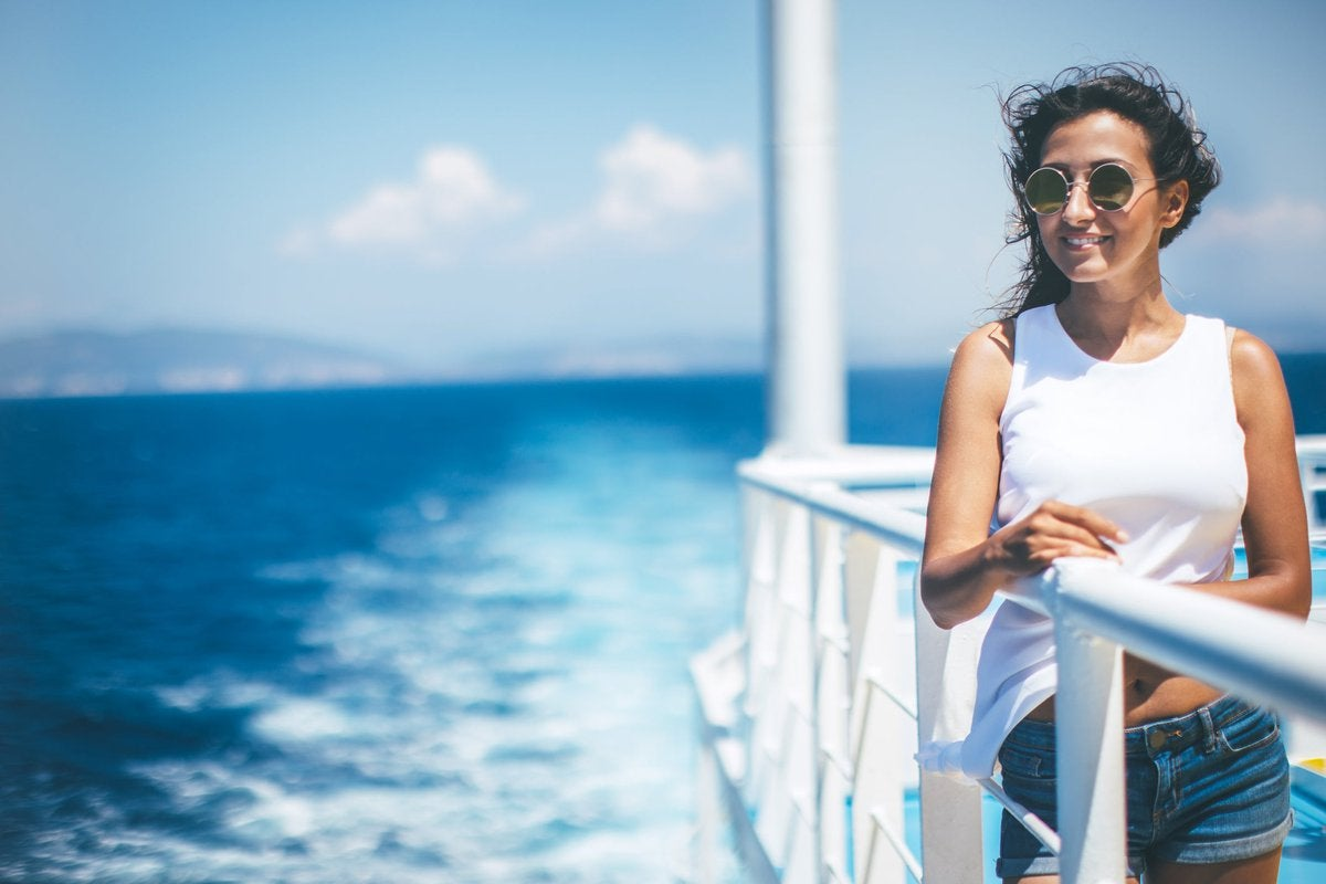 A smiling person standing at the railing of a cruise ship.