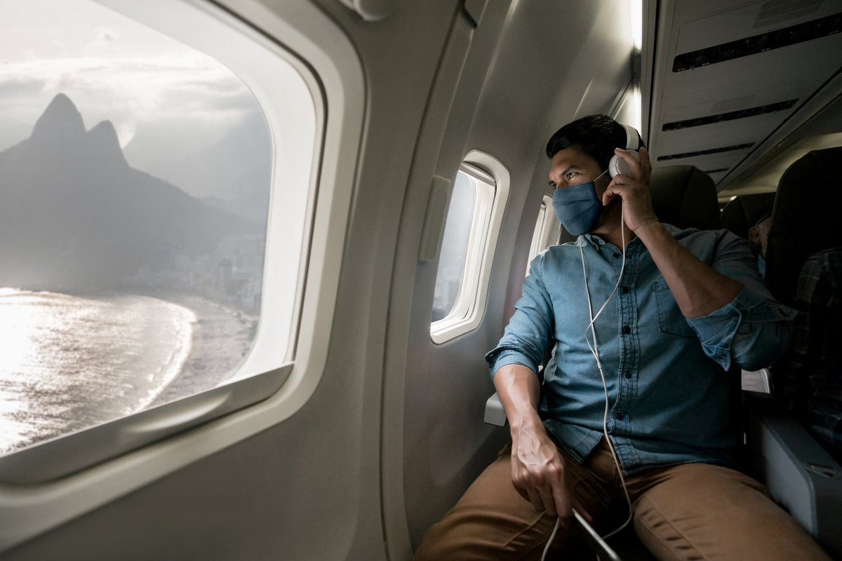 A person wearing a mask while sitting in a plane seat and looking out the window at a mountain next to the ocean.