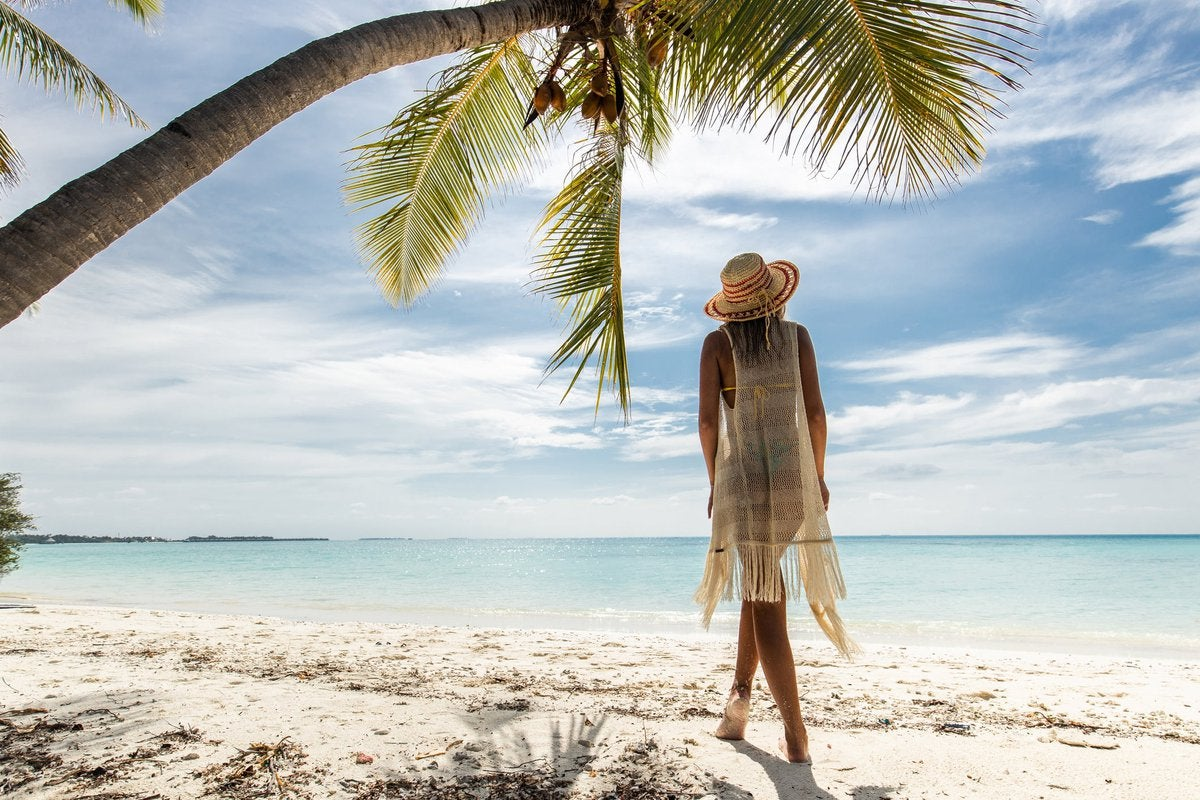 A person standing under a palm tree on a tropical beach.